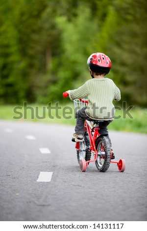 3 years old boy wearing safety bicycle helmet riding a bike - stock photo