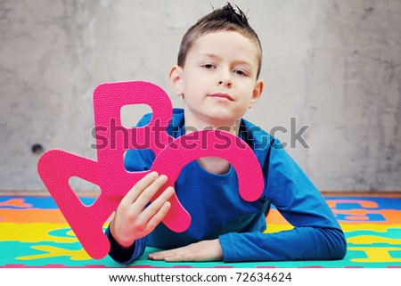 9 years old boy with alphabet letters - kids and family - stock photo