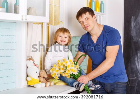 2-3 years old Caucasian boy is sitting on a table with yellow flowers. He is dressed in white raglan, blue jeans and sneakers. His father is standing next to him. - stock photo