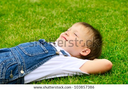 4 years old child lying on the grass. - stock photo