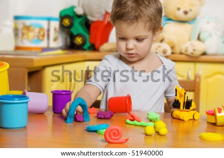 2 years old child playing plasticine in children's room - stock photo