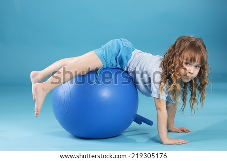 5 years old child playing with fitball l on blue studio background - stock photo