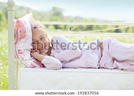 7 years old child resting on comfortable bed in spring field - stock photo
