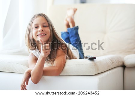 8 years old child watching tv laying down on a sofa at home alone - stock photo