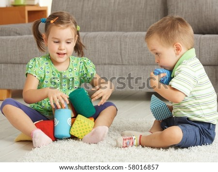 3-4 years old children playing together on the floor at home? - stock photo