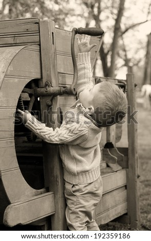 2 years old curious Baby boy managing with old agricultural Machinery on sepia brown color - stock photo