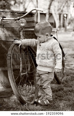 2 years old curious Baby boy walking around the old bike on sepia brown color - stock photo