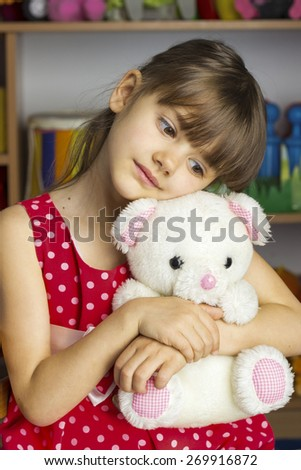 6 years old girl blond hair, red dress with white polka dots, toy white bear - stock photo
