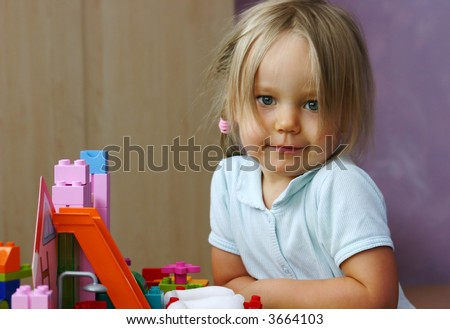 3 years old girl building a home from plastic blocks. - stock photo