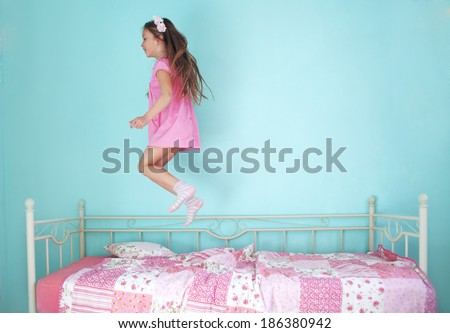 8 years old girl jumping on the bed at home - stock photo