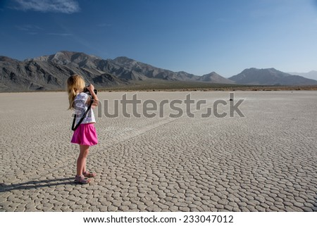 3 years old girl photographing sailing rocks at the Racetrack Playa. Death Valley, Nevada.