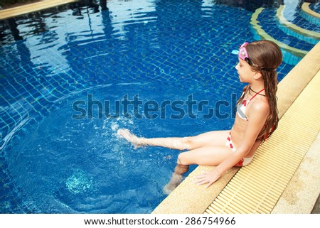 8 years old girl playing in swimming pool at hotel - stock photo