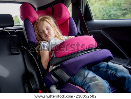 3 years old girl sleeping in a child seat during long road trip - stock photo