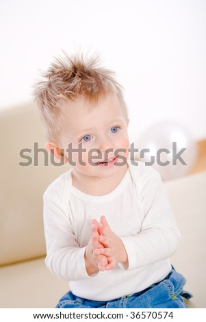 2 years old happy baby boy sitting on sofa clapping and smiling. - stock photo