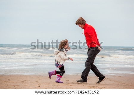 6 years old kid and her father running at the seacoast