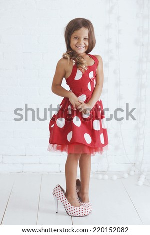 5 years old kid girl wearing stylish retro dress and heels posing over white background - stock photo