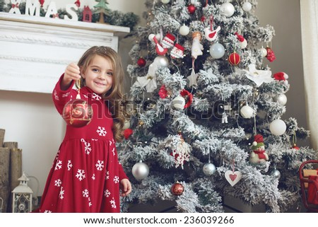 5 years old little girl decorating Christmas tree at home - stock photo