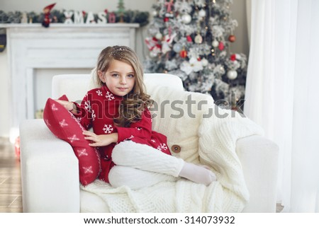 5 years old little girl sitting on cozy chair near Christmas tree in morning at home - stock photo