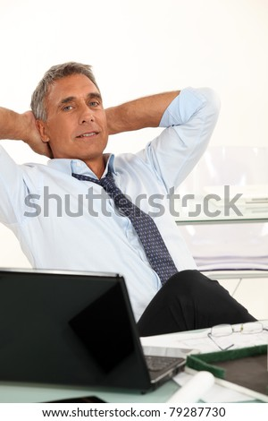 50-55 years old man dressed in shirt and tie is relaxing in his office - stock photo