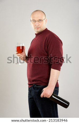 38 years old man holding Rose wineglass and black wine  bottle, man wear red sweater and dark blue jeans  - stock photo