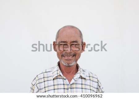63-years-old man was smiling on the white wall for background.