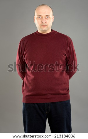 38 years old man wearing red sweater and dark blue jeans against grey background  - stock photo