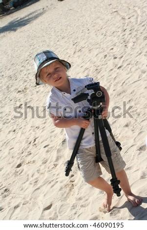 4 years old photographer on beach - stock photo
