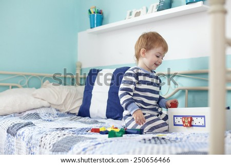 2 years old toddler playing with toys at the bedroom - stock photo