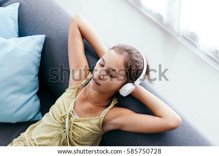 10 Years Old Tween Girl Relaxing On A Couch, Listening To Music In  Headphones And