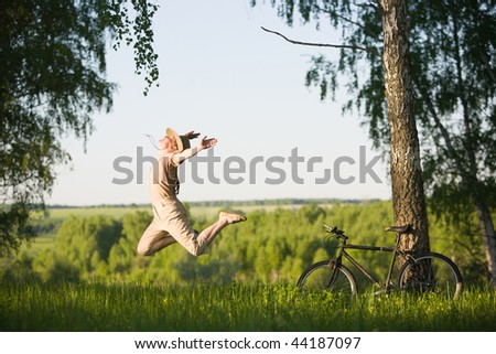 50 years old woman with bicycle jumping in  birch forest at summer - stock photo