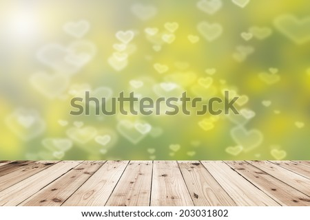 yellow Pastel Heart Bokeh and sunlight with wood floor - stock photo