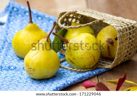 Yellow pears out of a basket - stock photo
