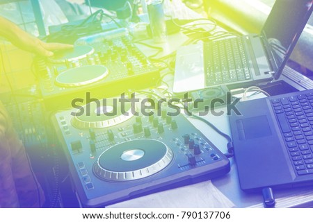 Yellow  tint , blue lines crazy atmospheric straboscope , Beautiful photo of black dj controller with hands dj , setup with stand laptop ,fader crossfader at event party.