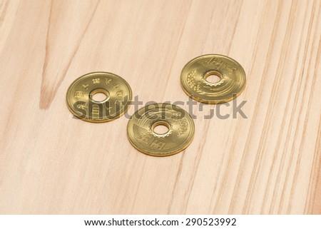 5 yen on wooden table - stock photo