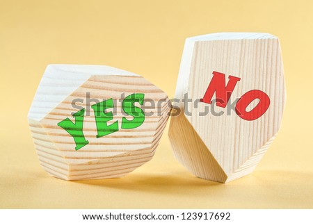 """""""Yes"""" and """"No"""" written on wooden blocks on yellow background - stock photo"""