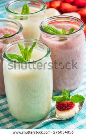 14.	Yogurt, smoothies, milkshake. Glass jars with a smoothie of strawberries and banana, melon, mint leaves. Smoothies. Close-up. Vertical shot. - stock photo