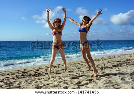 Young active women - girl friends high jump on a beach, Italy - stock photo