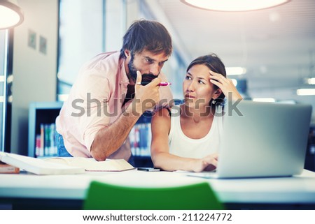 Young and attractive group of professionals having a discussion in office, beautiful business people using computer, two colleagues working together in the office - stock photo
