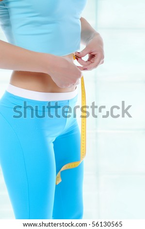 young athlete in sports uniform measure waist. - stock photo