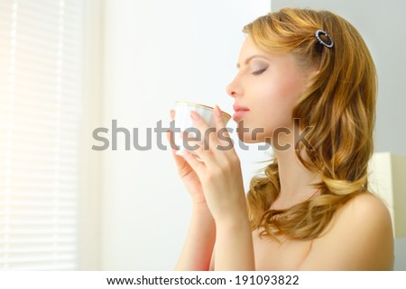 young attractive girl holding a cup of coffee in the morning - stock photo