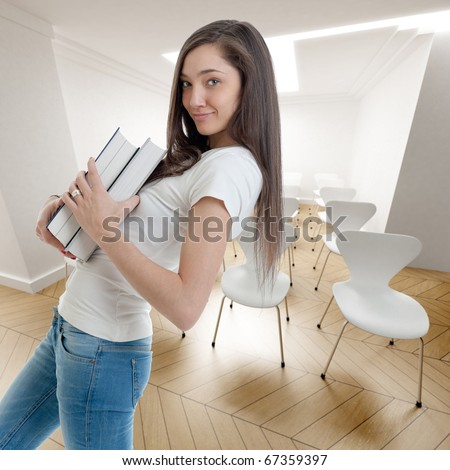 Young attractive woman carrying a pair of books in a conference room - stock photo
