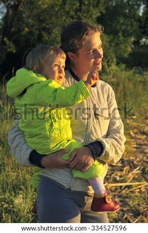 Young Attractive young mother holding a little girl in her arms at sunset light.  Walk in the autumn warm evening outdoors at sunset. Solar flare lights Woman and child.  - stock photo