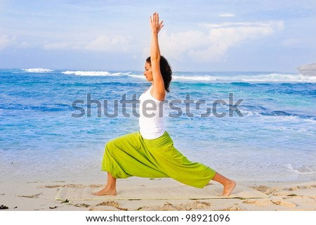 Young beautiful  girl doing yoga on the beach - stock photo