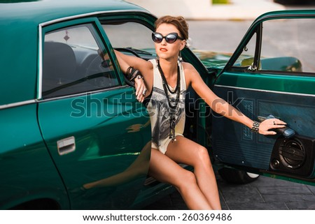 Young beautiful girl in glasses posing while sitting in the car - stock photo