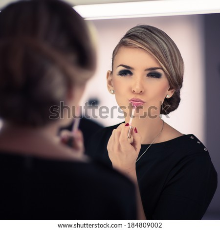 young beautiful woman does a house make up. looks at the reflection. Photo toned style instagram filters  - stock photo