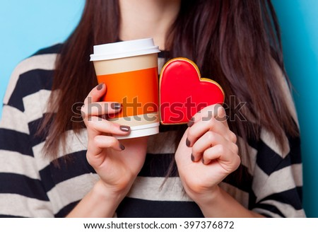 young beautiful woman holding cup of coffee and cookie standing on the blue background