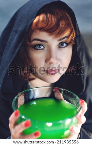 Young blond witch with poison in bowl - stock photo