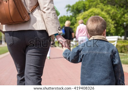 young boy holding hand in hand with his mother, outdoors in park.  - stock photo