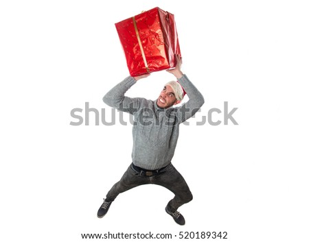 Young boy in a cap of santa claus holding a gift with his hands on his head isolated on white background