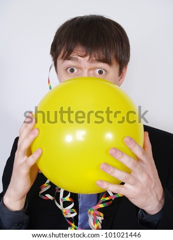 Young business man blowing up a yellow balloon on a white background. Facing camera.